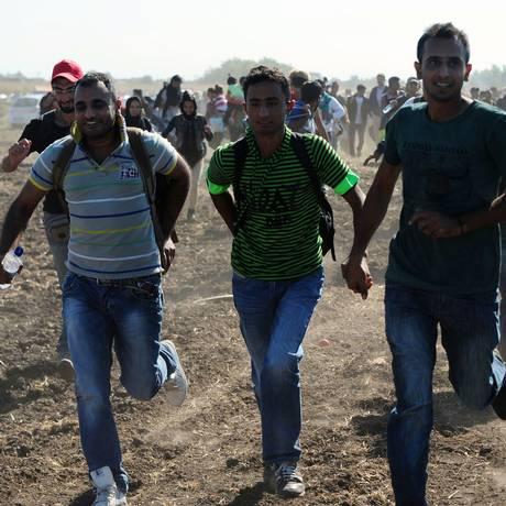 Imigrantes correm da polícia após romperem barreira perto de Roszke, na fronteira entre Hungria e Sérvia Foto: CSABA SEGESVARI / AFP