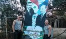 Sírios posam com imagens de apoio à aliança entre Assad e Putin Foto: Reprodução