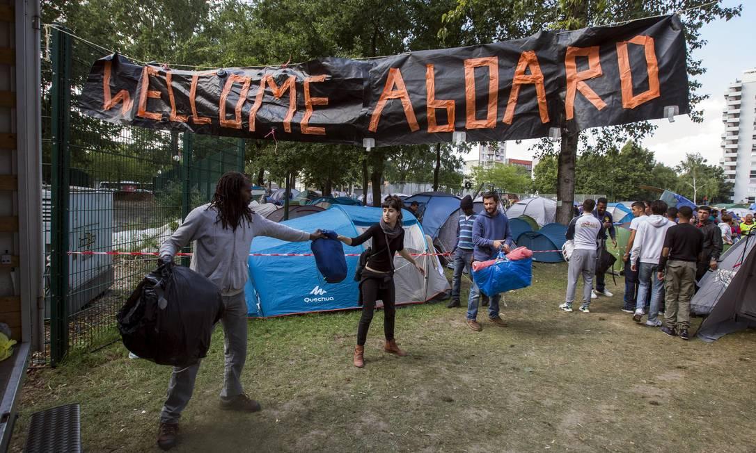 Diante de placa de boas-vindas, voluntários em Bruxelas trabalham para acolher refugiados chegando à Bélgica Foto: YVES HERMAN / REUTERS