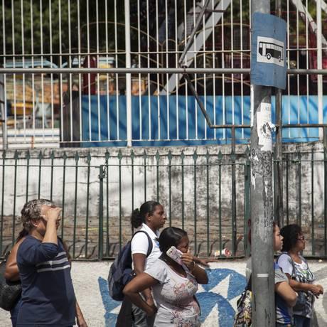 Passageiros esperam por ônibus e encaram sol quente: cena do cotidiano na Leopoldina Foto: Hermes de Paula / Agência O Globo