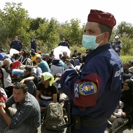 Um grupo de refugiados do Oriente Médio, em sua maioria a caminho da Alemanha, permanece sentado sob vigilância de policiais húngaros em Roszke Foto: MARKO DJURICA / Marko Djurica/REUTERS