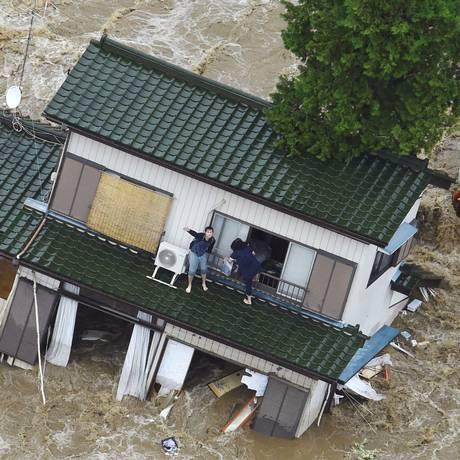 Japonesa acena para helicóptero enquanto sua casa é tomada por águas após cheia de um rio na cidade de Joso Foto: AP