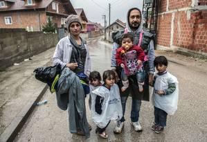 Muhamad Hasan ahmd, um imigrante sírio, sua mulher Wasfia Ahmd e seus quatro filhos esperam ônibus na aldeia de Miratovac perto da cidade sérvia de Presevo Foto: ARMEND NIMANI / AFP