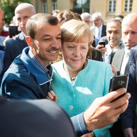 Requerente de asilo tira foto com Angela Merkel em Berlim Foto: BERND VON JUTRCZENKA / AFP