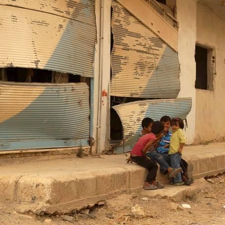 Crianças brincam perto de loja destruída em Deraa, no sudoeste da Síria Foto: STRINGER / REUTERS