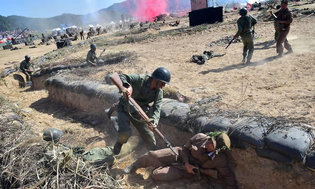 Soldados sul-coreanos, representam ambos os lados do conflito, e, encenam a batalha do rio Nakdong dentro de uma trincheira, durante a celebração do 65º aniversário da invasão ao país do norte JUNG YEON-JE / AFP