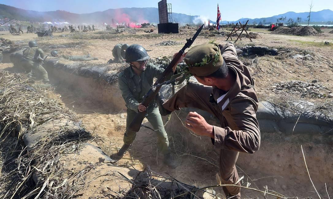 Soldados sul-coreanos, representam a batalha do rio Nakdong, dentro de uma trincheira JUNG YEON-JE / AFP