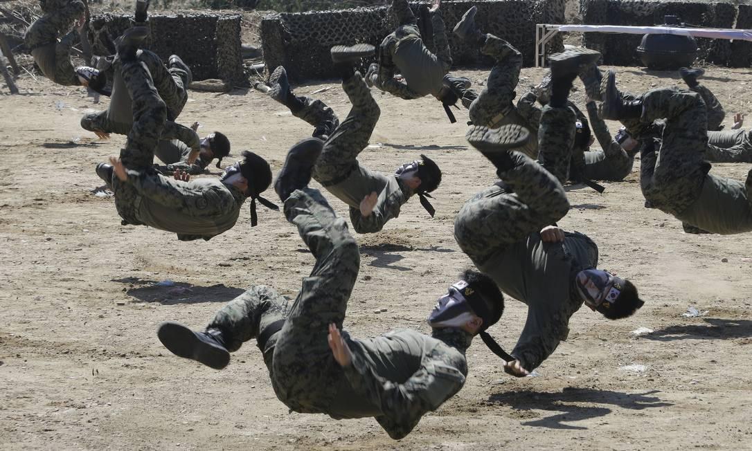 Soldados sul-coreanos demonstram golpes da artes marciais antes de encenarem a batalha do rio Nakdong, durante a celebração do 65º aniversário da invasão ao país do norte Ahn Young-joon / AP
