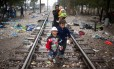 Uma mulher imigrante caminha com seus filhos por trilhos de trem na fronteira entre a Grécia e a Macedônia, perto da cidade de Gevgelija