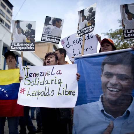 Manifestantes erguem cartazes em apoio a líder de oposição Leopoldo López durante seu julgamento em Caracas Foto: Ariana Cubillos / AP