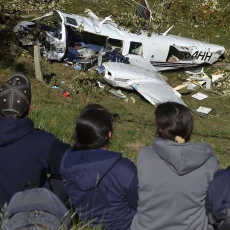 Pessoas observam o Piper PA-60, avião bimotor que caiu em uma área rural da cidade de San Predro de los Milagros Foto: RAUL ARBOLEDA / AFP