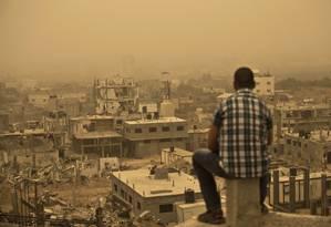 Em meio a uma tempestade de areia, palestino olha os prédios atingidos durante o último conflito entre Israel e Hamas Foto: AFP/8-9-2015