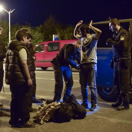 Imigrante sírio é revistado por policiais na fronteira com a Áustria em Freilassing. País reforçou segurança na divisa para conter fluxo de imigrantes ilegais Foto: GUENTER SCHIFFMANN / AFP