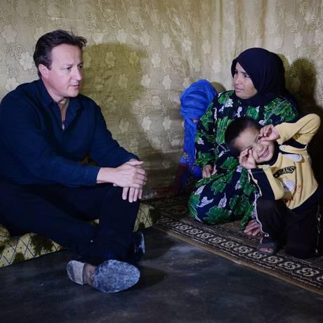Primeiro-ministro britânico, David Cameron, se reúne com famílias de refugiados sírios em um acampamento no Vale do Bekaa na fronteira da Síria com o Líbano Foto: Stefan Rousseau / AP