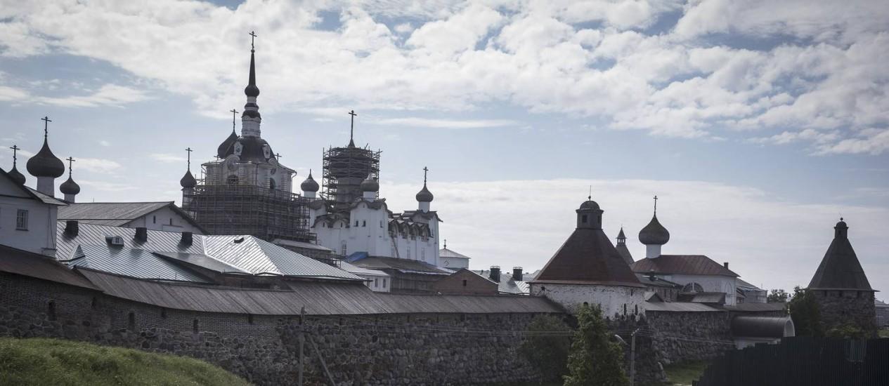 Peregrino caminha ao lado do Mosteiro Solovetsky nas ilhas Solovetsky, na Rússia Foto: SERGEY PONOMAREV / NYT