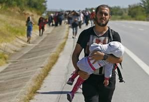 Um migrante sírio carrega um bebê enquanto caminha em direção à fronteira da Grécia em uma estrada perto de Edirne, na Turquia Foto: OSMAN ORSAL / REUTERS