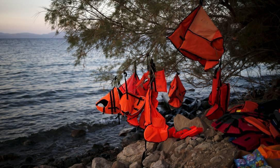 Coletes salva-vidas são deixados pendurados por refugiados que chegam à ilha grega de Lesbos. Ao fundo, a costa turca Foto: ALKIS KONSTANTINIDIS / REUTERS