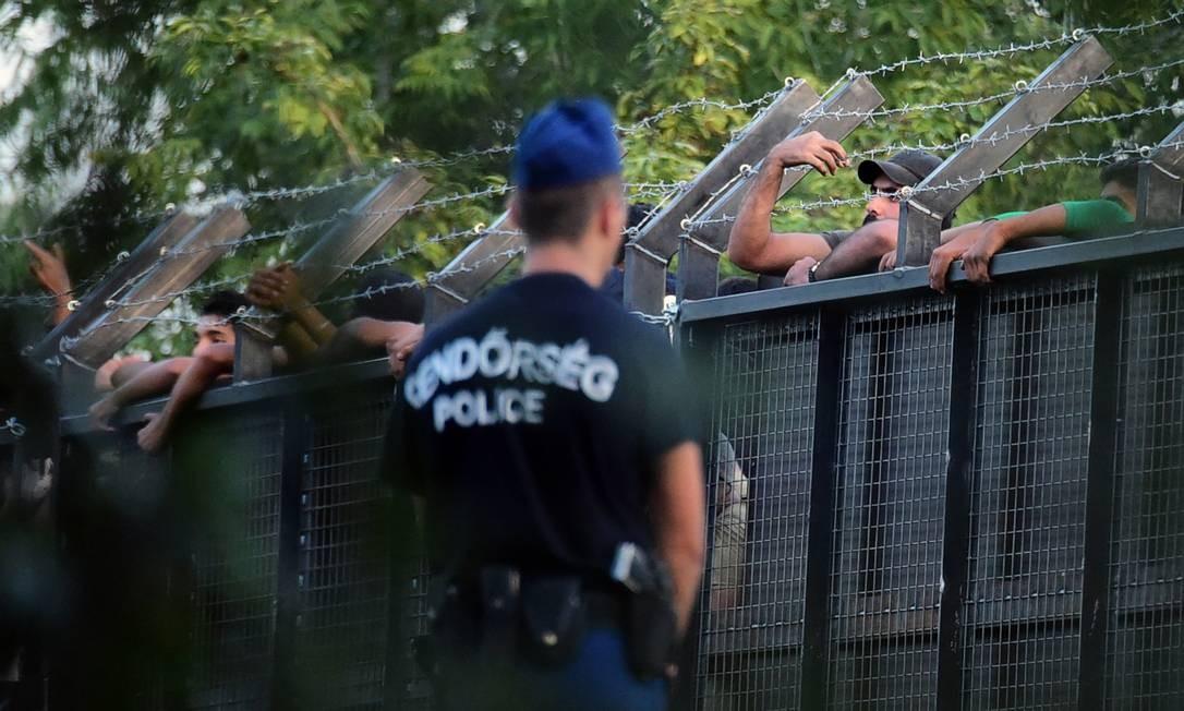Policiais húngaros montam guarda diante de refugiados tentando entrar no país a partir da Sérvia; Romênia seria novo alvo Foto: ATTILA KISBENEDEK / AFP