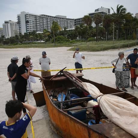 Transeuntes em Miami Beach conferem barco usado em viagem de Cuba ao estado Foto: JOE RAEDLE / AFP