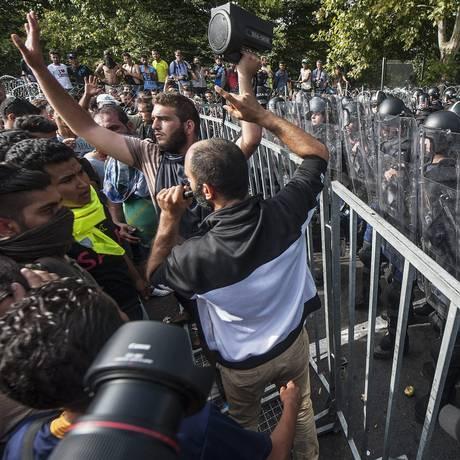 Imigrantes tentam atravessar fronteira da Sérvia com a Hungria mas são barrados pela polícia Foto: Sandor Ujvari / AP