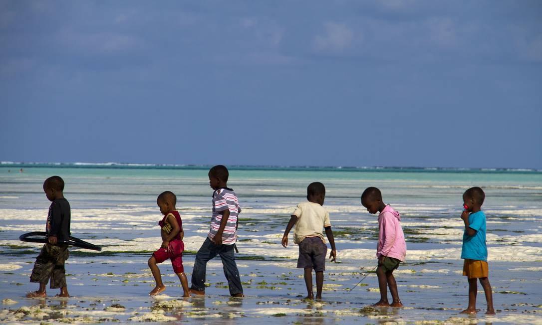Na praia, crianças brincam no mar de Zanzibar, na Tanzânia Foto: Volunteer Vacations / Divulgação