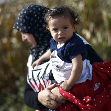 Mãe e sua bebê atravessam região em Tovarnik, na Croácia Foto: Matthias Schrader / AP