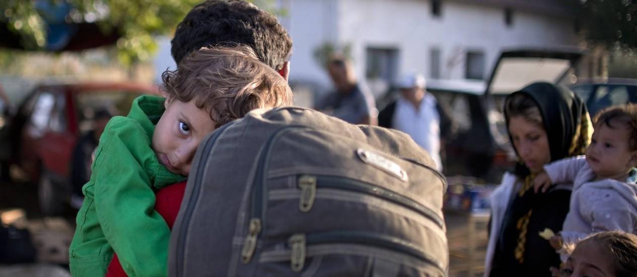 Imigrante carrega seu filho para um campo de refugiados depois de atravessar a fronteira Grécia-Macedônia perto da cidade de Gevgelij Foto: NIKOLAY DOYCHINOV / AFP