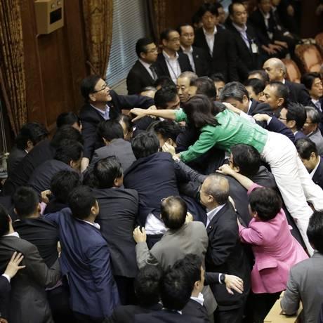 Parlamentares japoneses entram em confronto corporal em votação para nova legislação sobre a participação militar do país em conflitos internacionais Foto: Eugene Hoshiko / AP