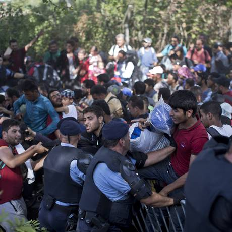 Migrantes tentam passar por linha policial em Tovarnik Foto: Marko Drobnjakovic / AP