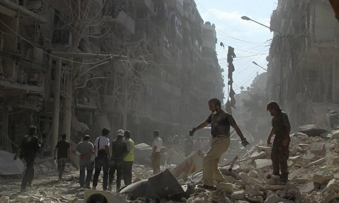 Vida sobre ruínas. Moradores e membros da defesa civil caminham pelo bairro Al-Shaar, em Aleppo: destruição total Foto: Abdalrhman Ismail/REUTERS