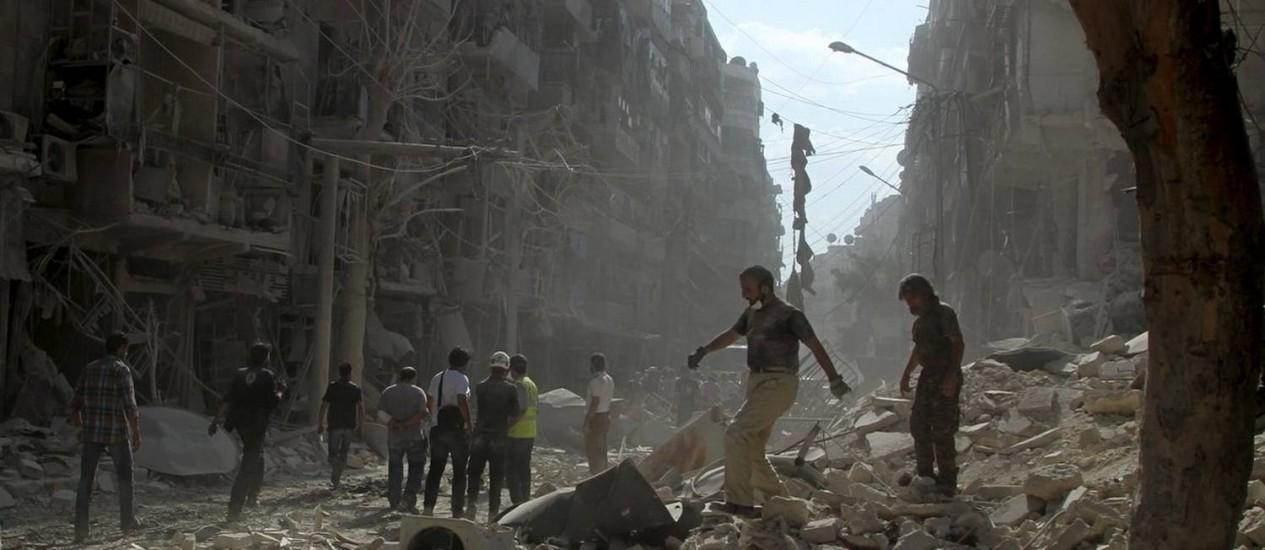 Vida sobre ruínas. Moradores e membros da defesa civil caminham pelo bairro Al-Shaar, em Aleppo: destruição total Foto: STRINGER / Abdalrhman Ismail/REUTERS