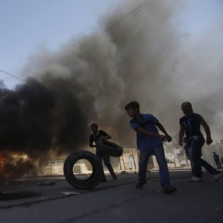 Perto da histórica mesquita de al-Aqsa, em Hebron, palestinos queimaram pneus Foto: MUSSA ISSA QAWASMA / REUTERS