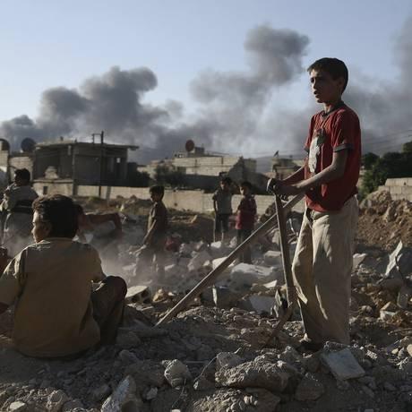 Crianças caminham sobre escombros após confrontos entre forças leais ao governo e a milícia islamista Exército do Islã, próximo à cidade de Douma, Leste da Síria Foto: BASSAM KHABIEH / REUTERS