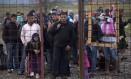 Imigrantes e refugiados fazem fila para se registrar em um acampamento após cruzarem a fronteira entre Grécia e Macedônia perto de Gevgelija Foto: NIKOLAY DOYCHINOV / AFP