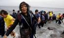Uma imigrante afegã exausta olha freneticamente para os seus filhos quando chega à ilha grega de Lesbos em um bote superlotado depois de atravessar uma parte do Mar Egeu a partir da costa turca Foto: YANNIS BEHRAKIS / REUTERS