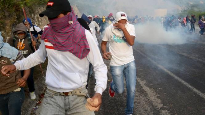 Estudantes de Ayotzinapa pegam pedras enquanto escapam de gás lacrimogêneo Foto: STRINGER/MEXICO / REUTERS
