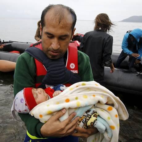 Refugiado síria carrega bebê após atravessar o Mar Egeu e chegar à Grécia a partir da Turquia Foto: YANNIS BEHRAKIS / REUTERS
