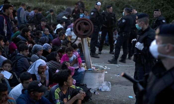 Polícia croata organiza fila de migrantes perto da fronteira com a Sérvia Foto: Marko Drobnjakovic / AP