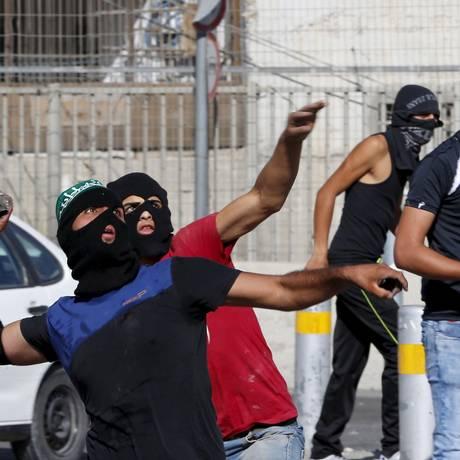 Palestinos jogam pedras contra forças de segurança israelenses em campo de refugiados na Cisjordânia Foto: AMMAR AWAD / REUTERS