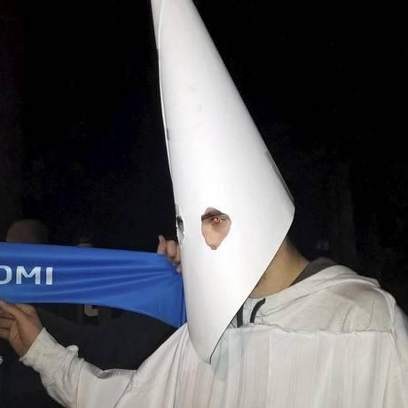 Manifestante com roupa do Ku Klux Klan protesta em frente a centro de acolhimento a refugiados Foto: MARKUS LUUKKONEN / AFP