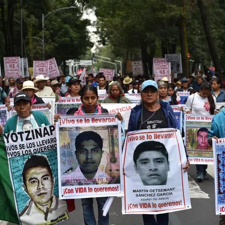 Revolta. Pais e familiares dos desaparecidos lideraram a manifestação carregando cartazes com fotografias dos filhos Foto: AFP/YURI CORTEZ
