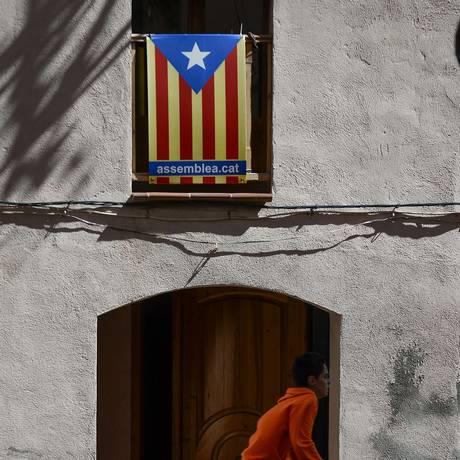 Ambição separatista. Um ciclista passa por cartaz pró-independência com a bandeira da Catalunha em Barcelona Foto: Joseph Lago/AFP