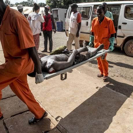 Homem ferido é carregado para o hospítal após o ataque de grupos armados muçulmanos contra um bairro cristão na capital da República Centro-Africana Foto: EDOUARD DROPSY / AFP