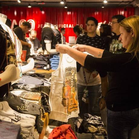 Consumidora observa camiseta à venda na Cidade do Rock Foto: Fabio Seixo / Agência O Globo