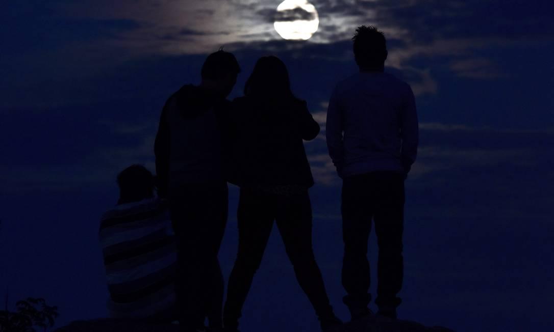 Pessoas assistem à superlua nascendo em Mississauga, Ontario, no Canadá. Pela primeira vez em mais de 30 anos, um eclipse lunar total vai acontecer combinado com uma superlua Nathan Denette / AP