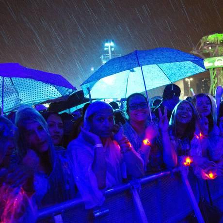 Público assiste ao show de AlunaGeorge embaixo de muita chuva Foto: Guito Moreto / Agência O Globo