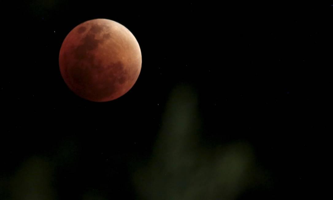 A lua, na cor vermelha escura, é coberta pela sombra da Terra durante eclipse lunar total em La Paz DAVID MERCADO / REUTERS