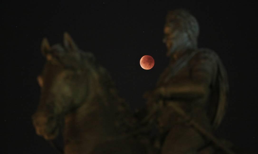 A superlua é vista acima da estátua de Henrique IV, durante eclipse lunar total em Paris Thibault Camus / AP