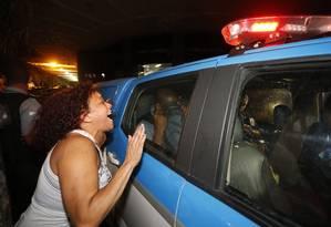 Uma moradora do Morro da Providência protesta contra um dos PMs, que esconde o rosto ao deixar a 4ª DP Foto: Domingos Peixoto / Agência O Globo