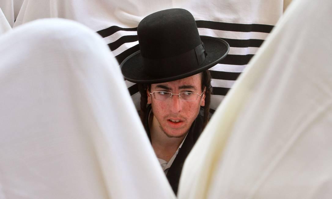 Judeu ortodoxo reza no Muro das Lamentações, na cidade antiga de Jerusalém, durante a cerimonia do Sucôt, ou Festa das Cabanas, feriado religioso celebrado após o periodo solene do Rosh Hashaná e Yom Kipur, para relembrar as peregrinações do povo judeu pelo deserto, a caminho da Terra Prometida. GIL COHEN MAGEN / AFP